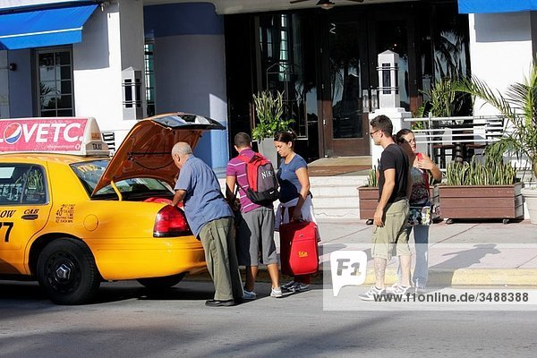 Florida  Miami Beach  ´Ocean Drive´  Park Central Hotel  entrance  guest  taxi  cab  man  woman  couple  driver  luggage  trunk  arrive  depart  transportation