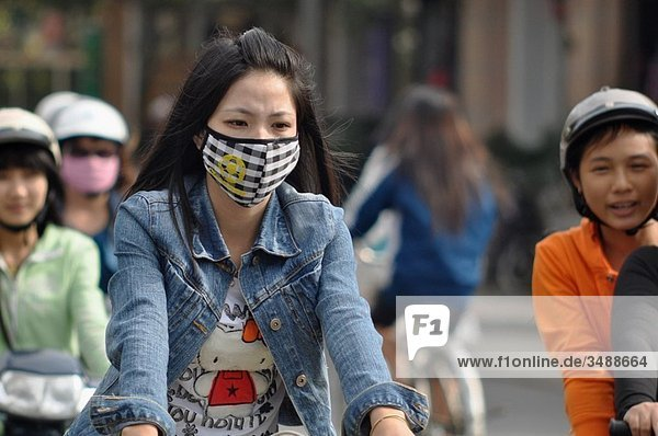 Hue (Vietnam): a woman wearing a mask against pollution while driving her bicycle in the urban traffic