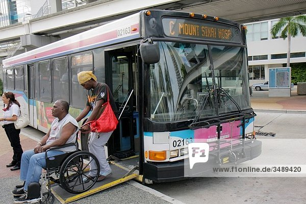 Florida  Miami  Omni Bus Station  Metrobus  public transportation  mass transit  bus  stop  electric wheelchair  disabled  physically impaired  Black  man  woman  couple  ADA  accessibility  ramp  boarding