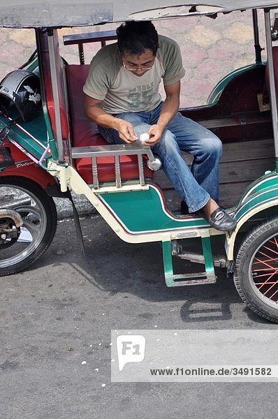 Phnom Penh (Cambodia): a tuk-tuk driver peeling a fruit and throwing the skin in the street while waiting for a customer