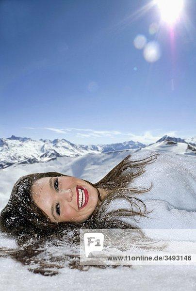 Frau lächelt im Schnee liegend