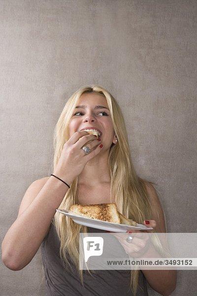 Junge Frau isst Sandwich