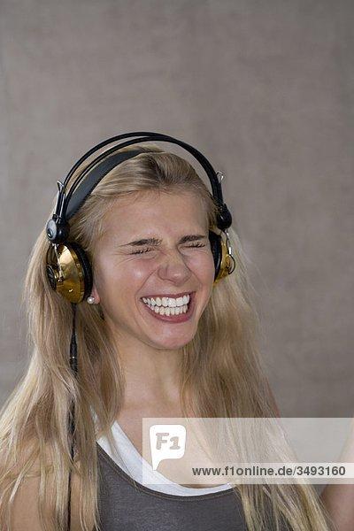 Teenagerin lächelt mit Kopfhörern
