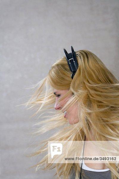 Junge Frau bewegt sich mit Kopfhörern