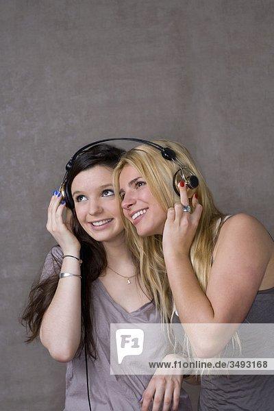 Teenagerinnen teilen sich Kopfhörer