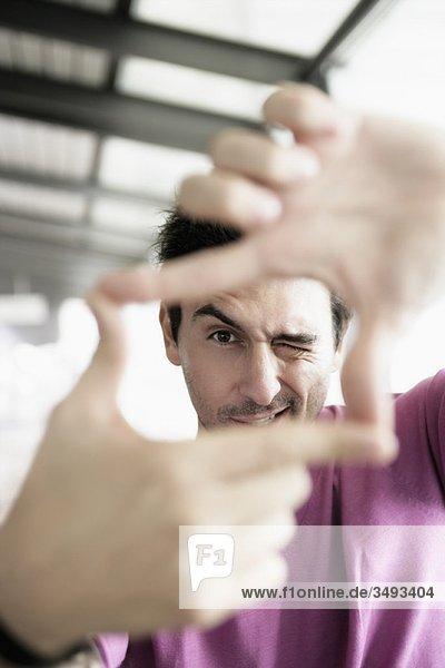 Mann schaut durch den Finger Mann schaut durch den Finger