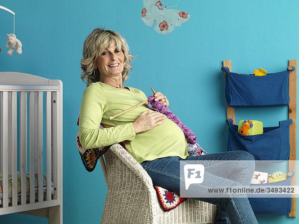 Schwangere reife Frau strickend