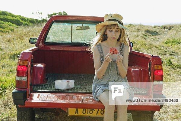 Mädchen isst Wassermelone auf der Rückseite des Trucks