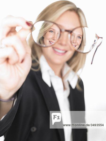 Frau hält eine Brille vor sich. Frau hält eine Brille vor sich.