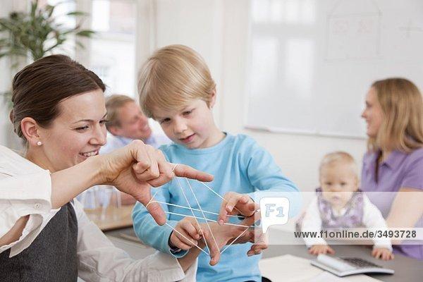 Geschäftsfrau  Junge spielt Streichspiel