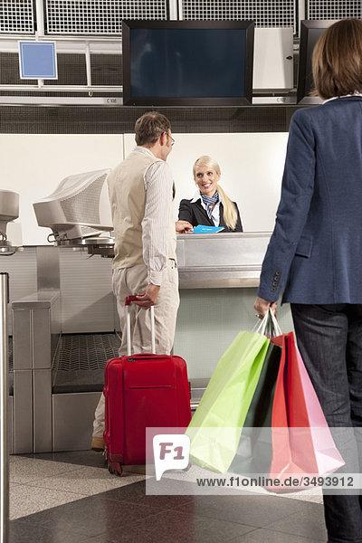 Ein Paar beim Einchecken mit Einkaufstaschen