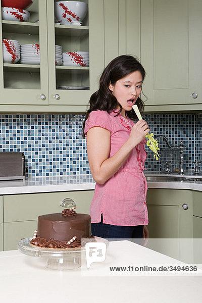 Junge Frau isst Sellerie und sieht Schokoladenkuchen