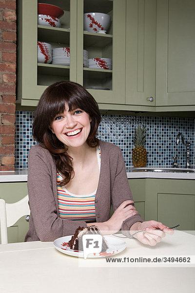 Junge Frau isst Schokoladenkuchen