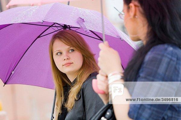 Two girlfriends under umbrellas