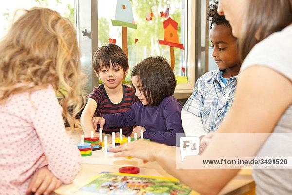 Kindergärtnerin und Kinder spielen an einem Tisch