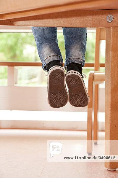 Beine baumeln von einem Tisch  Flachwinkelansicht