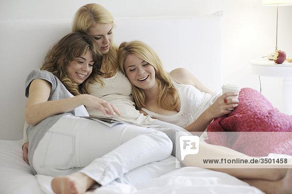 Drei Schwestern lesen eine Zeitschrift und amüsieren sich