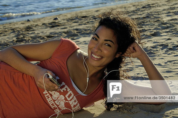 Frau liegt am Strand und hört mit Kopfhörern Musik