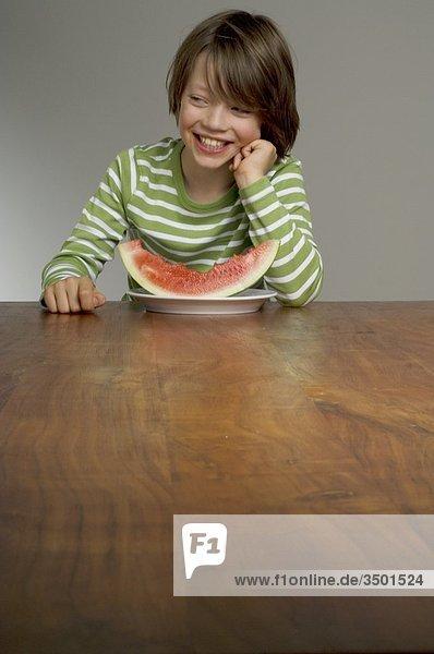 Junge isst eine rote Melone