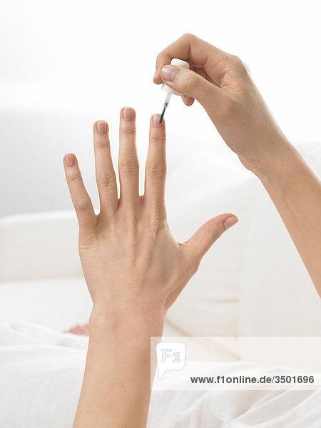 Frau lackiert ihre Fingernägel