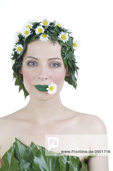 Frau mit Blättern auf dem Kopf  grünen Lippen und einer Blüte im Mund Frau mit Blättern auf dem Kopf, grünen Lippen und einer Blüte im Mund