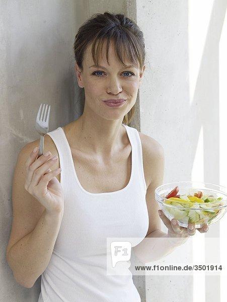 Junge Frau isst stehend einen Salat