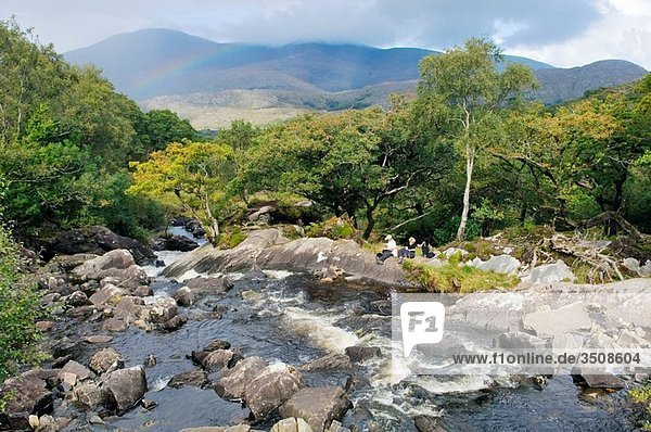 Young man and woman picnic beside Galway's River at Galway's Bridge above Upper Lake  Killarney National Park  Co Kerry  Ireland