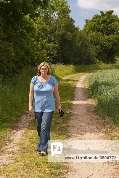 A woman in her thirties walking alone down a country farm track in the uk countryside in spring
