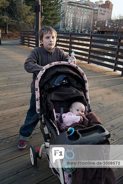A boy pushes his sister in a stroller through Riverfront Park  Spokane  Washington  USA