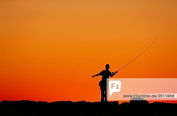 Boy fishing from a jetty at sunset  Menemsha  Martha´s Vineyard