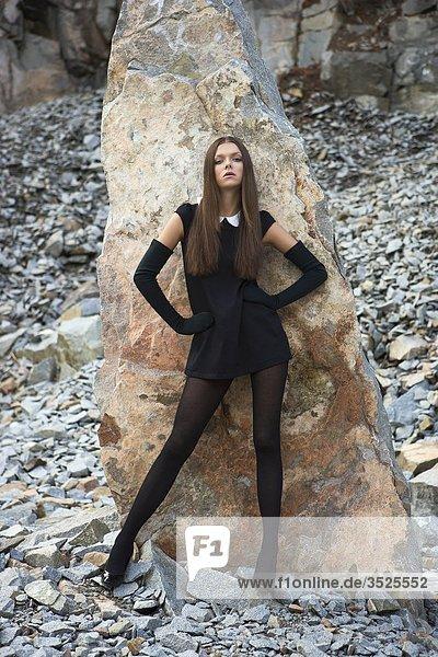 Frau stehend mit Rock im Hintergrund