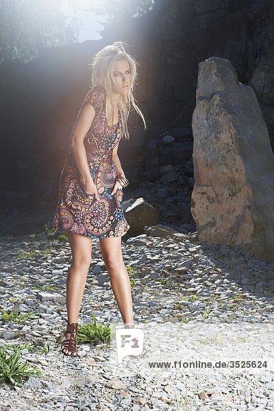 Junge Frau im Steinbruch stehend  Wegsehen