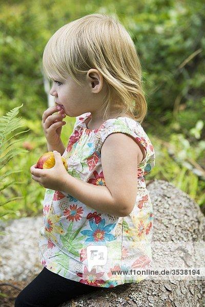 Kleine Mädchen hält Pfirsich
