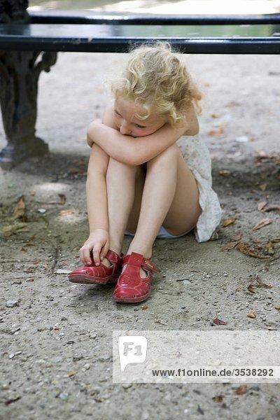 Mädchen sitzen auf Boden allein
