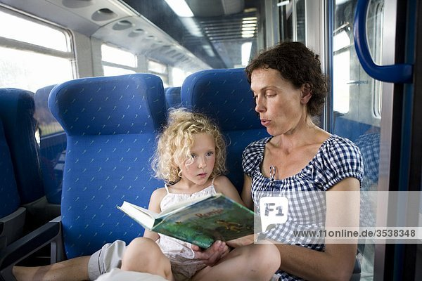 Mother reading to daughter in train