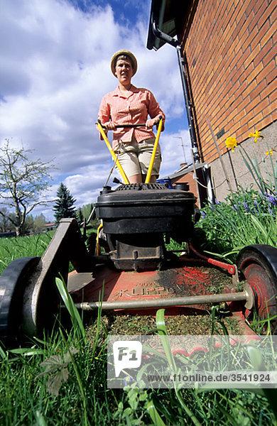 Scandinavia  Sweden  Ostergotland  Woman mowing lawn
