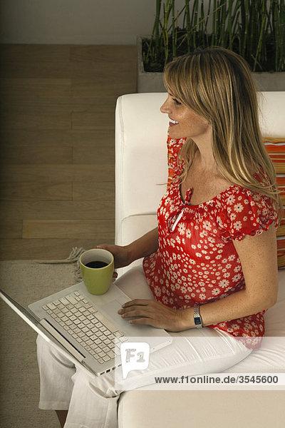 Frau entspannt sich zu Hause bei einer Tasse Kaffee  mit Laptop-Computer
