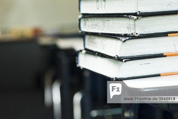 Stapel von Lehrbüchern auf dem Schulpult