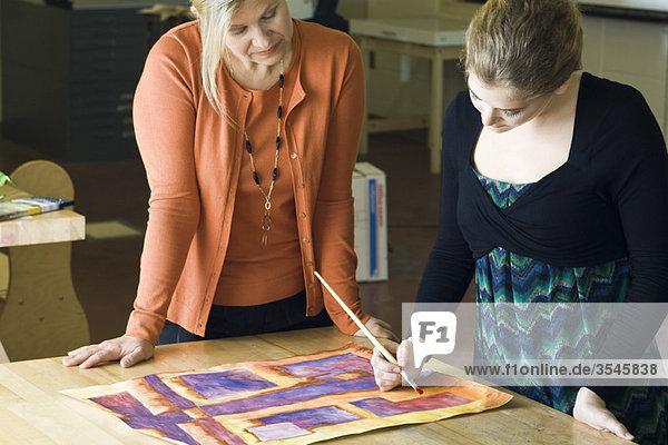 Kunststudent malt mit Aquarellen  während der Lehrer beobachtet.
