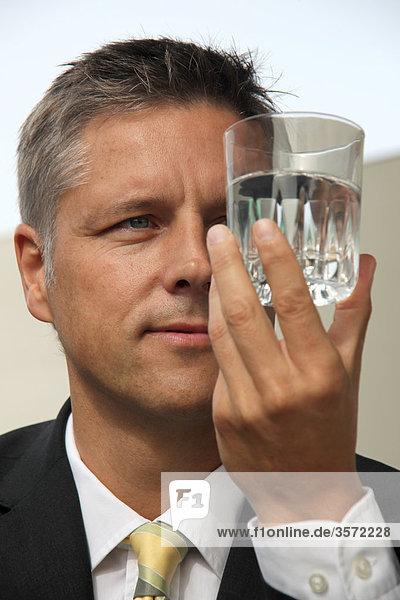 Geschäftsmann hält ein Wasserglas