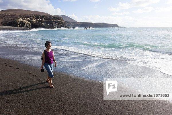 Frau geht am Strand spazieren  Ajuy  Fuerteventura  Spanien