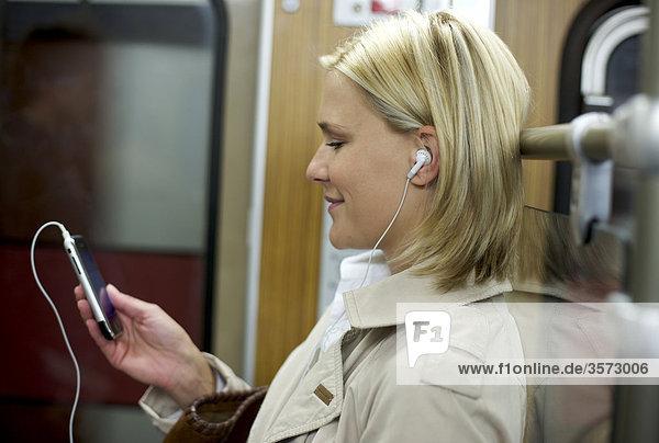 Frau hört Musik mit dem Handy in der U-Bahn  Profil