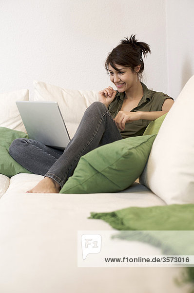Lächelnde Frau im Wohnzimmer mit Laptop