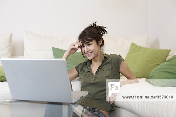 Smiling woman in living room looking at laptop