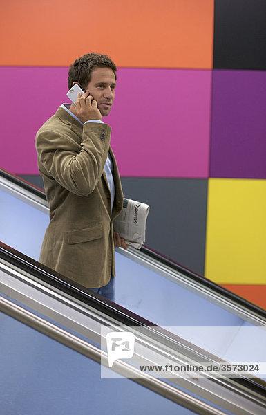 Mann telefoniert auf einer Rolltreppe