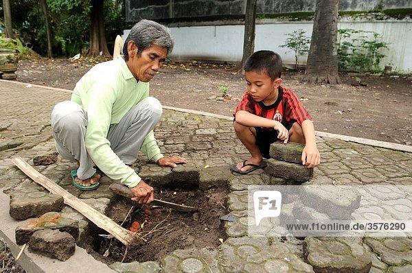 man and son paving at kraton kanoman in cirebon  java  indonesia
