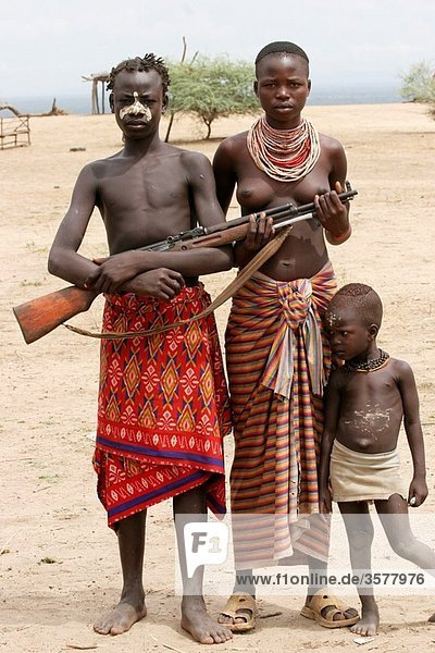 Africa  Ethiopia  Omo Valley  Daasanach tribe family Man carrying rifle
