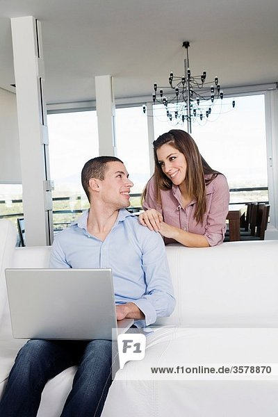 Portrait of a young couple using laptop on the sofa in the living room