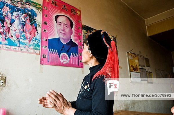 A Hani / Akha woman looking at a picture of her hero - Mao Tse-Tung.