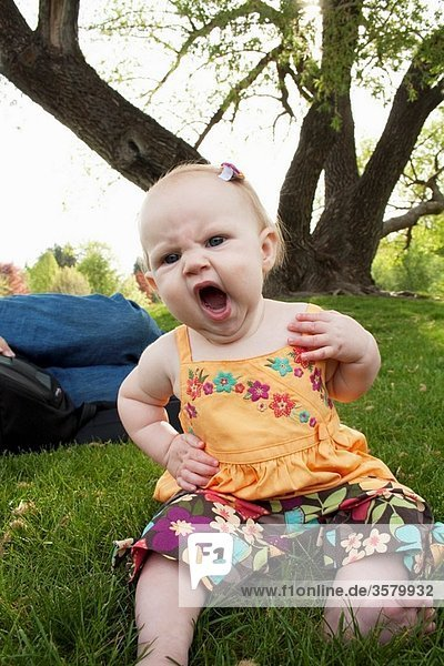 A girl  7 months old  yawning and sitting in the grass at a park